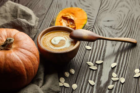 Autumn pumpkin soup with sour cream in wooden bowl with spoon and fresh pumpkins on dark background