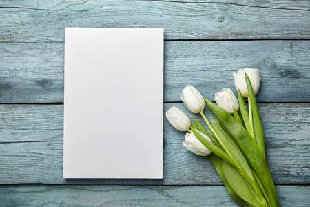 White canvas and bouquet of spring flowers on old light blue wooden background, flat lay. Blank canvas and white tulips on table, mockup, front view