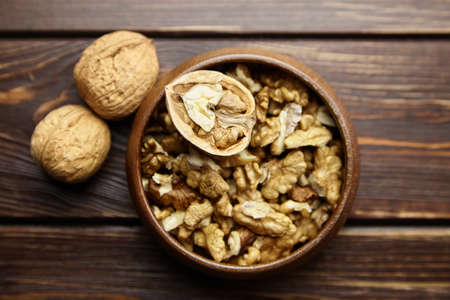 Walnuts in round bowl on wooden table. Half of walnut and dry seeds on brown background, healthy food, top view