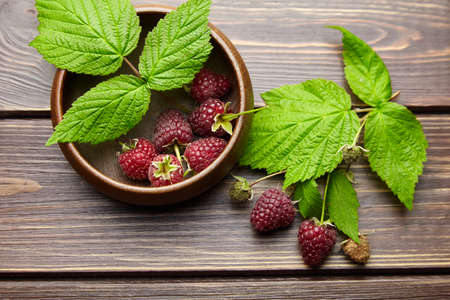 Fresh raspberry red berries with green leaves in bowl on wooden table background, ripe juicy raspberries top view
