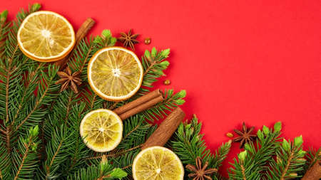 Holiday background with Christmas tree or pine branches, dried oranges, anise stars and cinnamon sticks spices. New Year or Christmas border, top view, copy space. Stock fotó