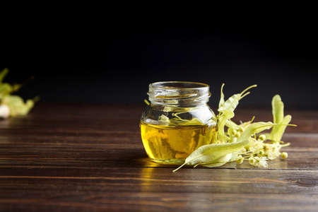 Linden honey in glass jar and linden flowers on wooden table. Sweet flower honey