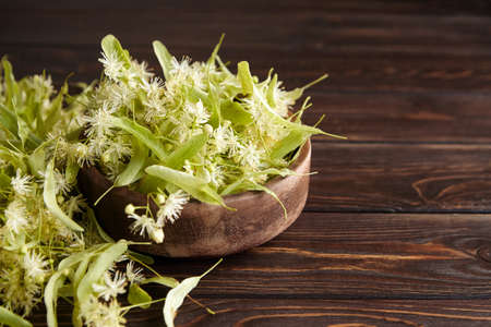 Linden flowers in wooden bowl on table. Fresh tilia flowers