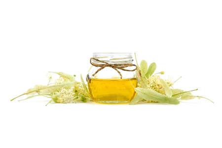 Linden honey in glass jar and linden flowers isolated on white background. Sweet flower honey Standard-Bild