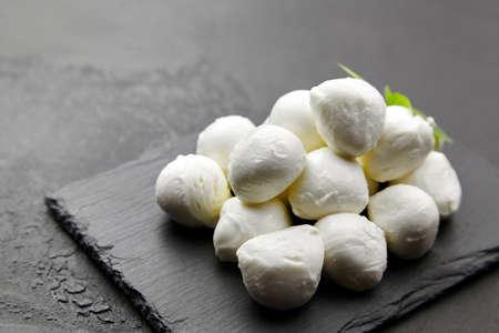 Small mozzarella cheese balls on black slate board over dark concrete background, italian food concept Standard-Bild