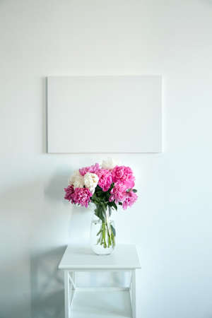 Canvas mockup hanging on white wall and vase with pink flowers on wooden shelf. Blank artistic canvas