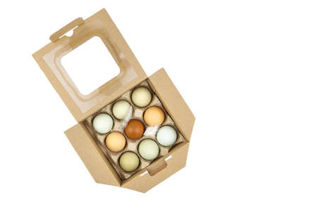Chicken eggs in tray isolated on white background. Nine eggs in cardboard box, top view Standard-Bild