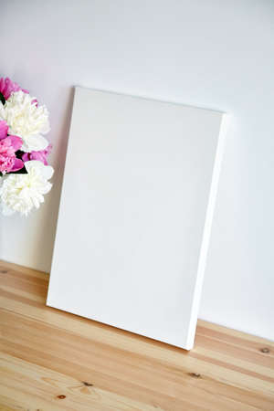 Canvas mockup with pink flowers on wooden table on white wall background. Blank artistic canvas