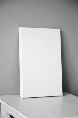 White canvas mockup, blank picture on white wooden table in interior with gray wall