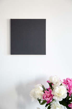 Black canvas mockup hanging on white wall and pink flowers. Blank artistic canvas