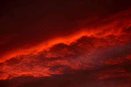 Red sunset sky with dramatic clouds. Scenic clouds illuminated by red sunlight Standard-Bild