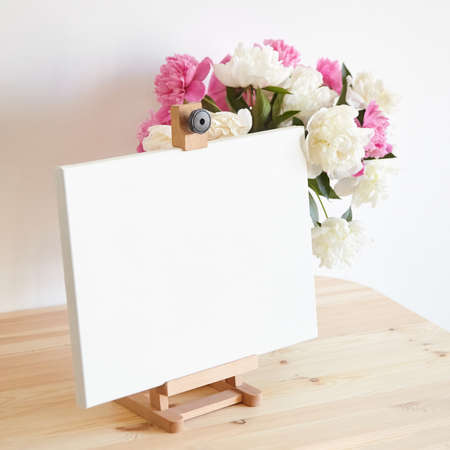 Canvas mockup on easel and pink flowers on wooden table on white wall background. Blank artistic canvas Standard-Bild