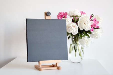 Black canvas mockup on wooden easel and vase with pink flowers on table on white wall background. Blank artistic canvas