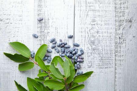 Honeyberry (Lonicera caerulea) on gray wooden background, top view. Heap of sweetberry honeysuckle (Haskap berry) with fresh green leaves Standard-Bild