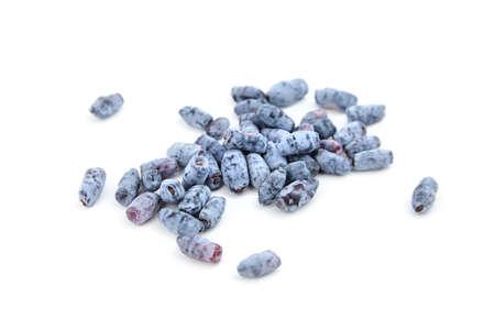 Honeyberry (Lonicera caerulea) sweet berries isolated on white background. Heap of scattered sweetberry honeysuckle (Haskap berry)