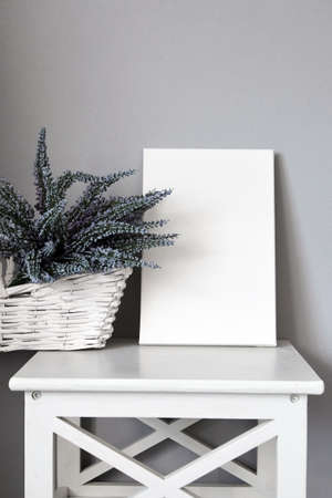 Canvas on shelf with lavender flowers in white basket, interior decor, gray wall. Blank picture. Stretched cotton canvas 免版税图像