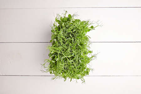 Fresh microgreens on white wooden background, top view. Young pea shoots on table, healthy food