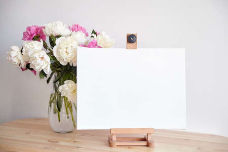 Canvas mockup on easel and pink flowers on wooden table on white wall background. Blank artistic canvas 免版税图像