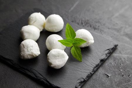 Small mozzarella cheese balls with basil on black slate board over dark concrete background, italian food concept