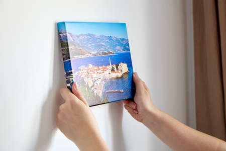 Canvas print with gallery wrap. Woman hangs photography on white wall. Hands holding photo canvas print with image of old town of Budva in Montenegro