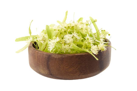 Bowl with linden flowers isolated on white background. Fresh tilia flowers