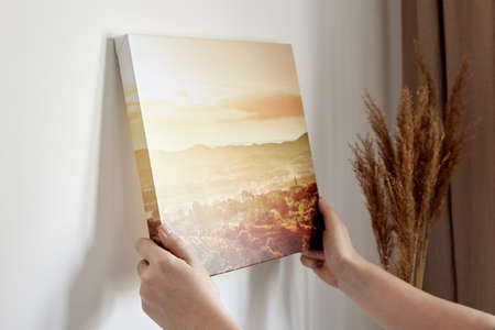 Canvas print with gallery wrap and dry grass interior decor. Woman hangs landscape photography on white wall