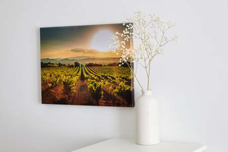 Canvas photo print with gallery wrap and flowers in vase, interior decor. Landscape photography hanging on white wall. picture with vineyard
