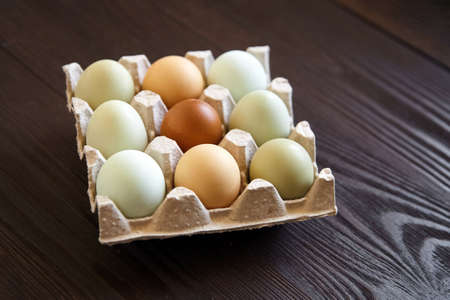 Chicken eggs in tray on wooden table. Nine eggs in cardboard holder on brown table
