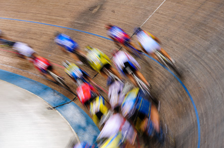 velodrome: Indiscernible pack of track cyclists racing past on the turn of a velodrome