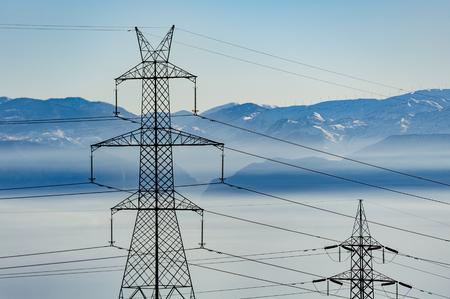 torres el�ctricas: torres de alta tensi�n con monta�as en el fondo Foto de archivo