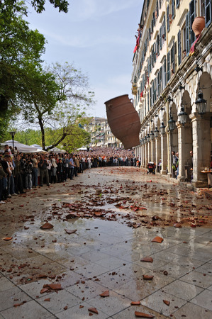 CORFU, 그리스 -2009 년 4 월 18 일 : 11시에 거룩한 토요일에, 관습에 따라, Corfians는 성령의 토요일에 Liston Spaniada 산책로에서 발코니에서 물로 채워진 주전
