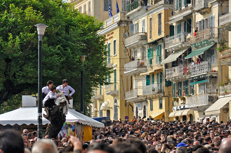 tree position: CORFU, GREECE - APRIL 18, 2009: Children perched on a tree for a better view of the Epitaph procession, enjoying their elevated position above a crowded square.