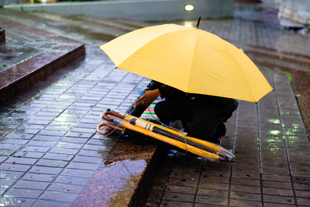 unlawful: A migrant or refugee selling umbrellas in the rain outside a metro station in Athens, Greece. Stock Photo