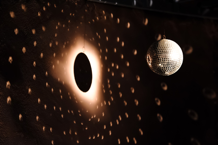 Spotlight on disco ball close to a wall creating an illusion of a sun, planet, stars and eclipse in space