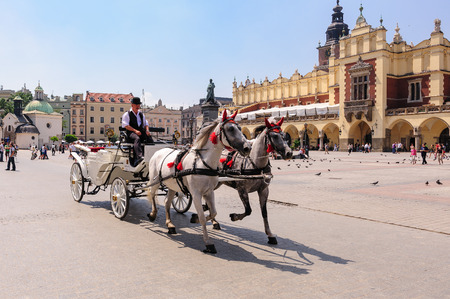 hackney carriage: KRAKOW, POLAND - JULY 2, 2009: Horses and carriage at the old town grand square Editorial