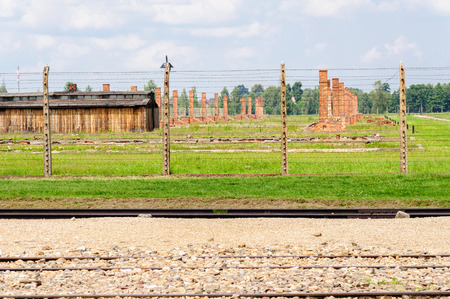 death camp: Auschwitz II - Birkenau, Sector II heating ovens and chimneys behind the inner electrified fence, as viewed from the rail tracks and ramp