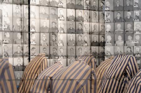 prisoners: OSWIECIM, POLAND - JULY 3, 2009: Auschwitz I - Birkenau display in Block 15 of prisoners striped uniforms and photos of victims
