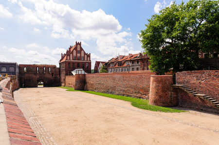 moat wall: TORUN, POLAND - JULY 7, 2009: Gothic St. George guild house and the moat between old and new towns Editorial