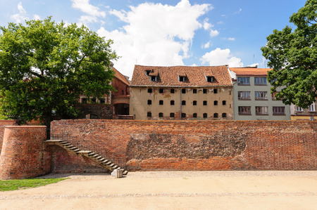 granary: TORUN, POLAND - JULY 7, 2009: Rear view of an old granary and the West Gate from inside the moat between old and new towns