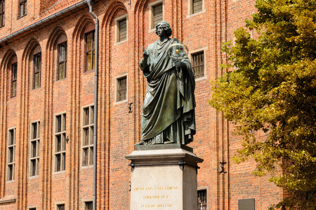stare miasto: TORUN, POLAND - JULY 7, 2009: Monument of Nicolaus Copernicus holding an astrolabe in front of the old town hall on a granite pedestal bearing a Latin inscription in gold letters