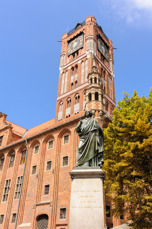 stare miasto: TORUN, POLAND - JULY 7, 2009: Monument of Nicolaus Copernicus holding an astrolabe in front of the old town hall and tower on a granite pedestal bearing a Latin inscription in gold letters