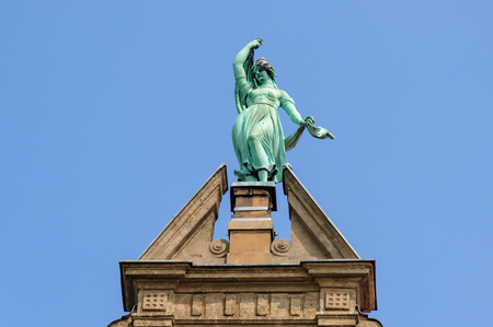 collegium: TORUN, POLAND - JULY 7, 2009: Statue of Fortune atop the gable of the Collegium Maximum building of the Nicolaus Copernicus University