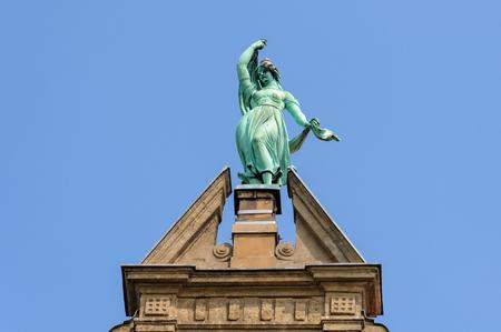 stare miasto: TORUN, POLAND - JULY 7, 2009: Statue of Fortune atop the gable of the Collegium Maximum building of the Nicolaus Copernicus University