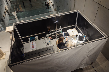 caryatids: ATHENS, GREECE - JANUARY 28, 2011: Restoration and conservation work on the Caryatids at the New Acropolis Museum. Conservator using laser to remove surface contamination.