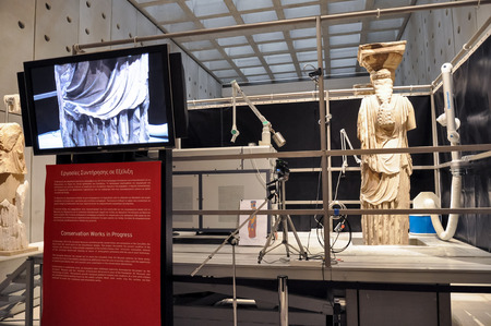 caryatids: ATHENS, GREECE - JANUARY 28, 2011: Restoration and conservation work on the Caryatids at the New Acropolis Museum. Laser equipment on platform to remove surface contamination.