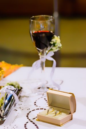 triad: ATHENS, GREECE - OCTOBER 25, 2015: Wedding rings and chalice with wine on a table in preparation for a wedding, at church Agia Fotini Ilissos church Editorial