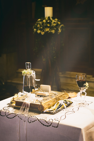 triad: ATHENS, GREECE - OCTOBER 25, 2015: Wedding rings, Bible, marital Crowns and chalice with wine on a table in preparation for a wedding, at church Agia Fotini Ilissos church Editorial