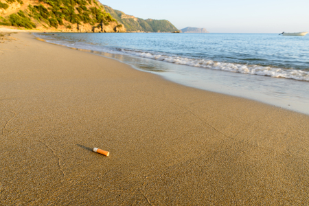 put away: Cigarette bud thrown away at a clean sandy beach shore