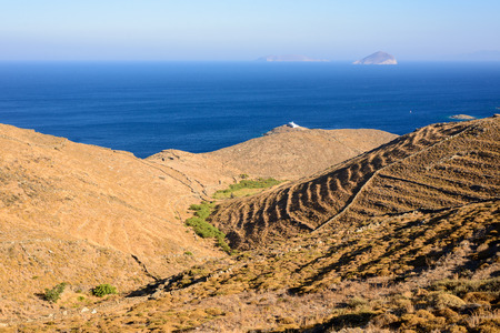 kyklades: Abandoned terraced hills covered with shrubs and church of St. John Eleimonas at a spit in the distance