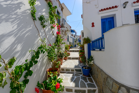 kyklades: Typical stone slated alley with limewashed houses and bougainvilleas in Kythnos, Greece Stock Photo
